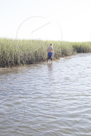 boy in blue board shorts walking on brown lake water beside green grass under white clouds during daytime photo