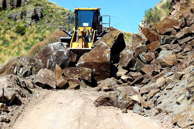 mechanical shovel rocks moving on country road photo