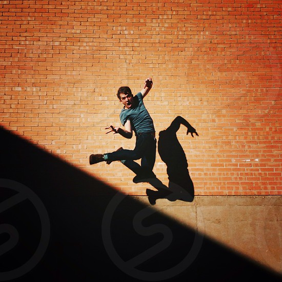 man in blue round neck t shirt jumping photo