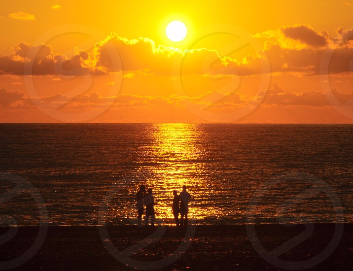 people standing on shore with a view of sun and sea photo