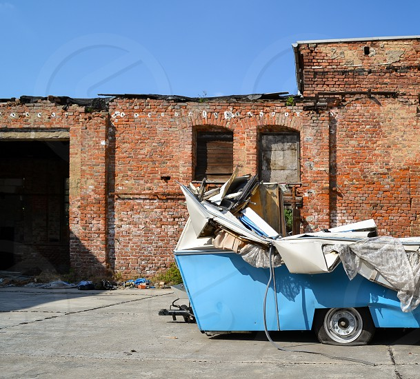 Caravan destroyed old broken accident factory brick wall outdoors plates crushed photo