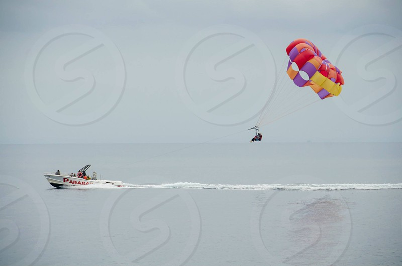 person riding in white power boat pulling person riding in red yellow and orange parachute photo