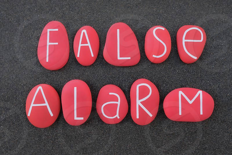 False alarm text composed with red colored and carved stones over black volcanic sand photo