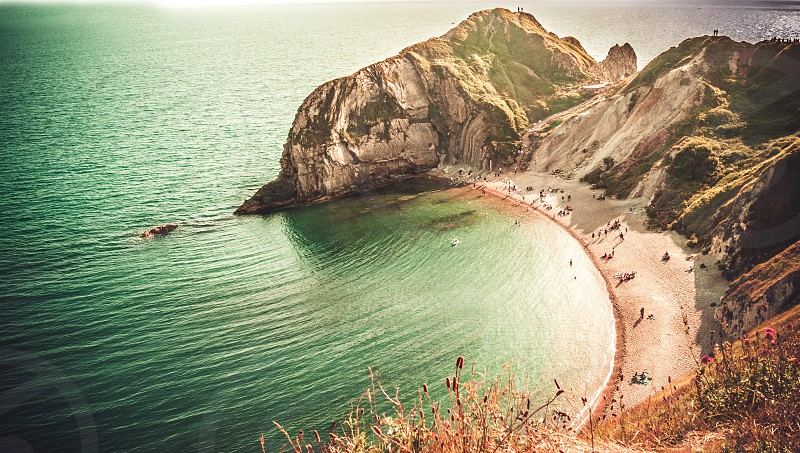 A very popular beach of sand and fine pebbles on the east side of Durdle Door Jurassic Coast Dorset England United Kingdom  photo