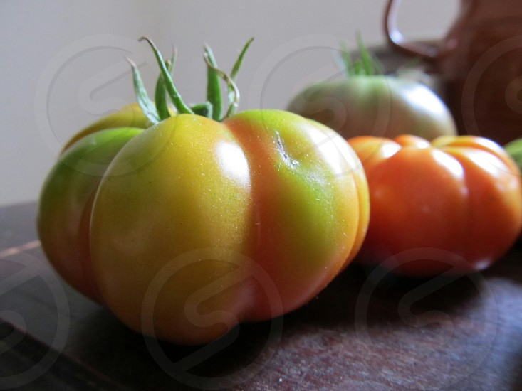 Heirloom tomatoes on counter yellow red and green photo