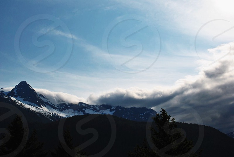 snow capped mountain beside white clouds under blue sky photo