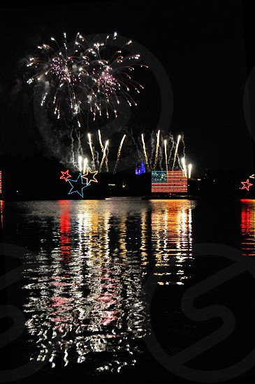 Red white and blue stars and American flag floats on a lake with fireworks photo