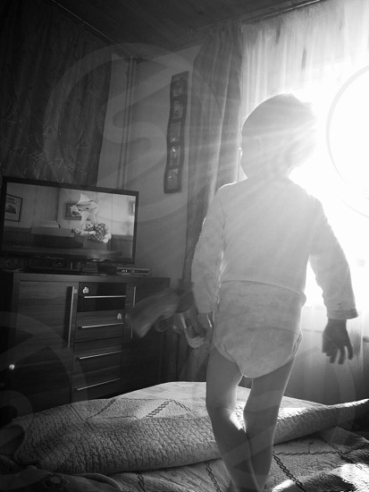 toddler in white onesie near tv and window curtains photo