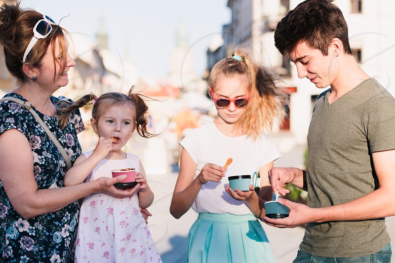 Family spending time together in the city centre enjoy eating ice cream on a summer day. Mother toddler and teenage girl and boy spending quality time on sunny afternoon eating sweet dessert. Downtown area in the background photo