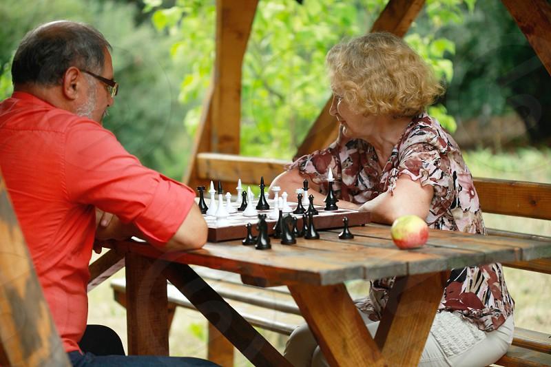 elderly couple playing chess in gazebo photo