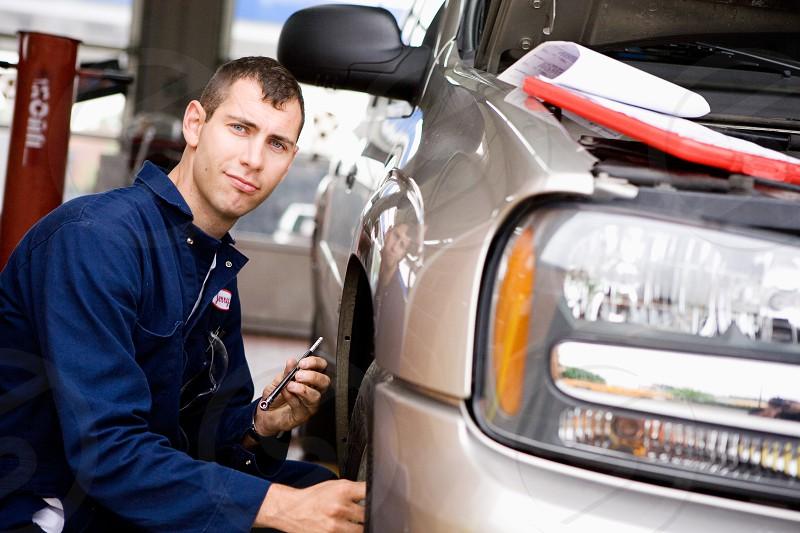 Mechanic Inspecting Truck  mechanic suv truck tire wheel man occupation job working employee auto shop shop repair shop photo