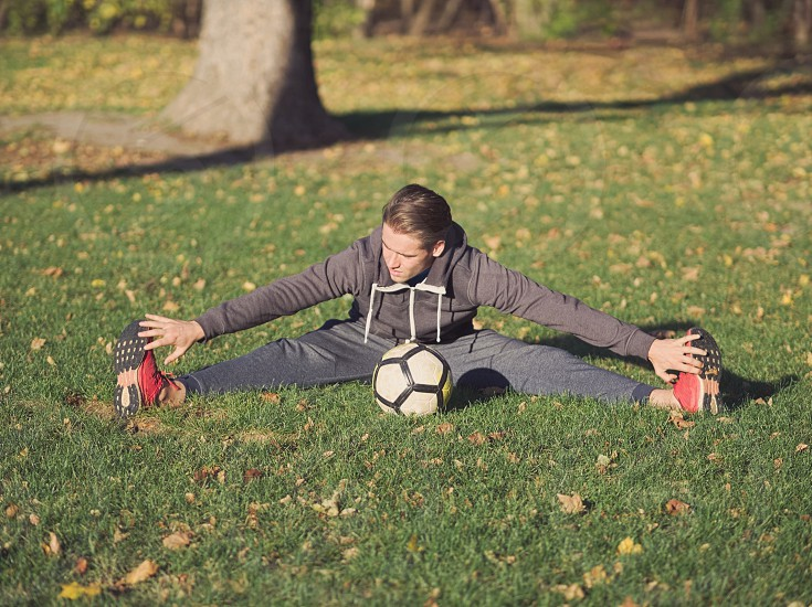 Soccer Player Stretching with Football in the Park on a Sunny Autumn Day photo