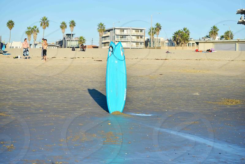 cyan surfboard in beach sand during daytime photo