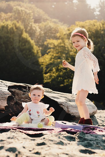 girl in white dress with baby in white dress on beach photo