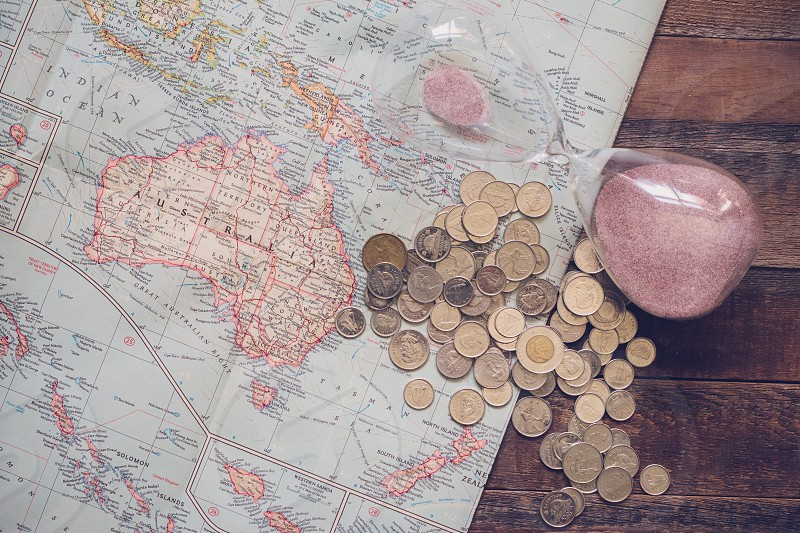 Vintage map showing the Pacific Ocean and Australia with Canadian coins and hourglass photo