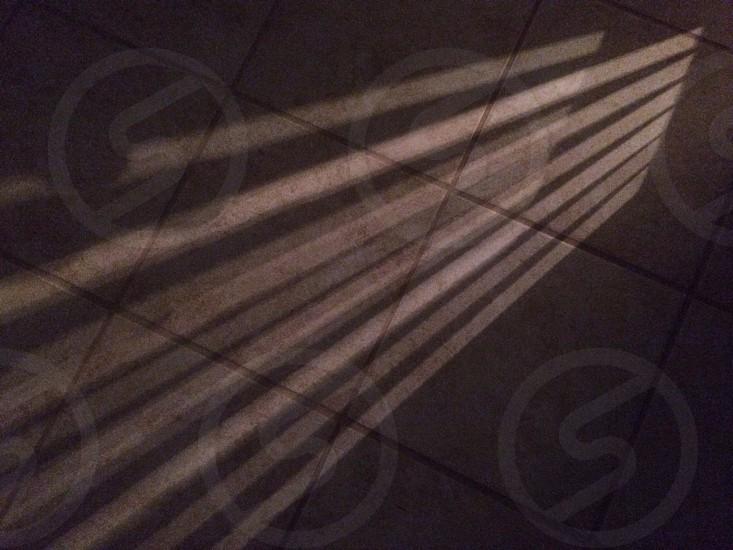 sun rays on grey floor tiles photo