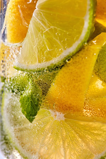 In a clear glass mint leaf slices of lime and lemon with bubbles. Macro photo of summer cooling mojito photo