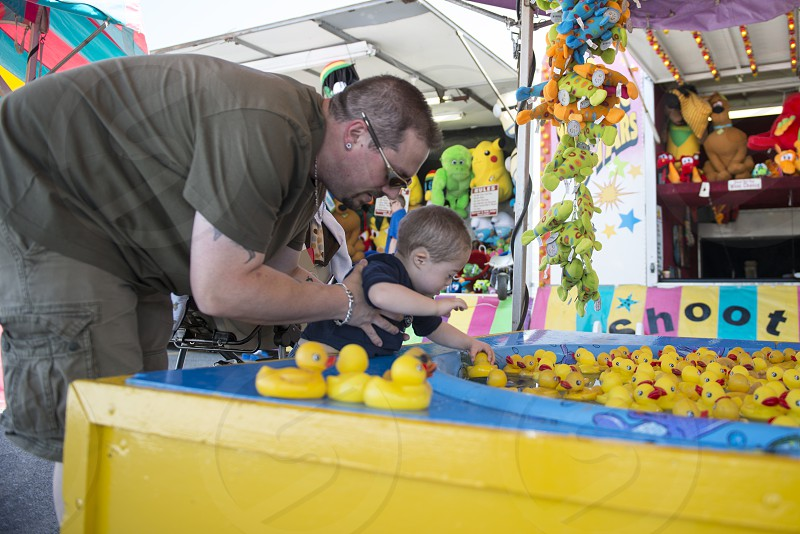 Daddy helping his Son (with Special Needs - Down syndrome) pick a duck in the duck pond at the local fair. photo