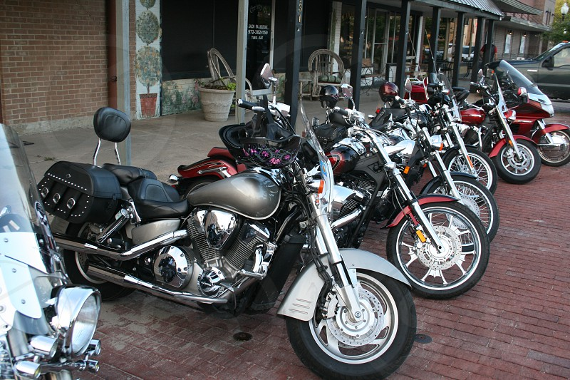 Row of motorcycles on the side of a brick road in a small country town. photo