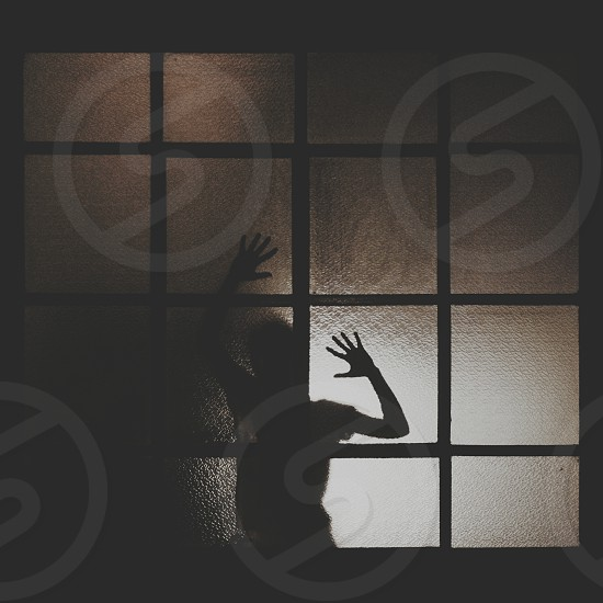 person's silhouette on glass framed wall photo