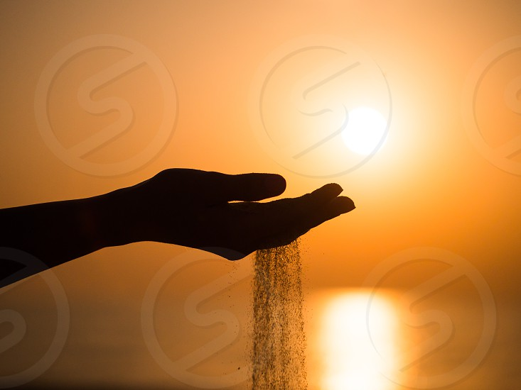 Silhouette of a young girl's hand pouring sand from a beach against a yellow sky at sunset photo
