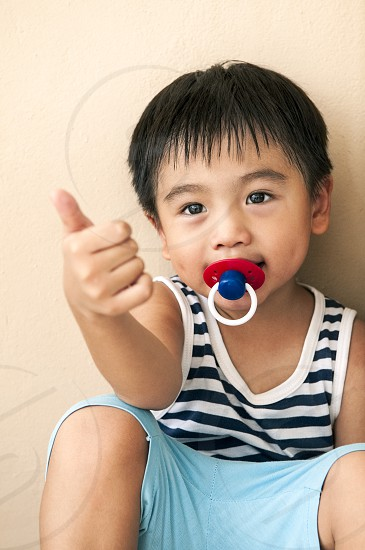 Portrait of a cute young boy with pacifier in mouth and gesturing thumb up. photo