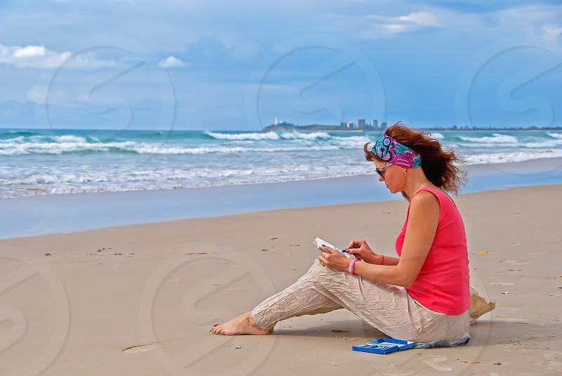 a woman sitting on the beach and drawing photo