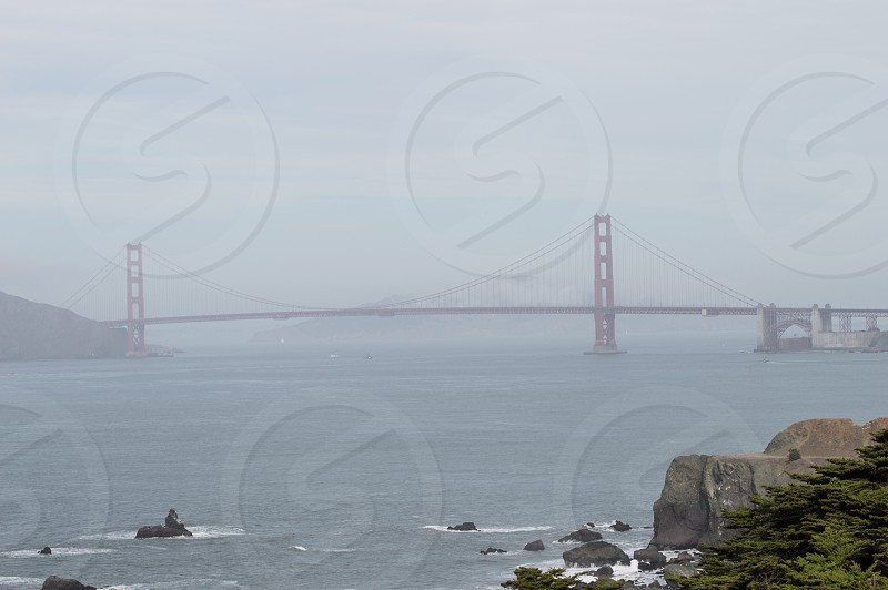View of San Francisco Bay Bridge. Fog hovers over the water as well as the bridge. photo