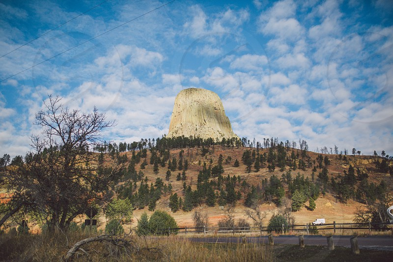 devil's tower under blue sky with white clouds during daytime photo