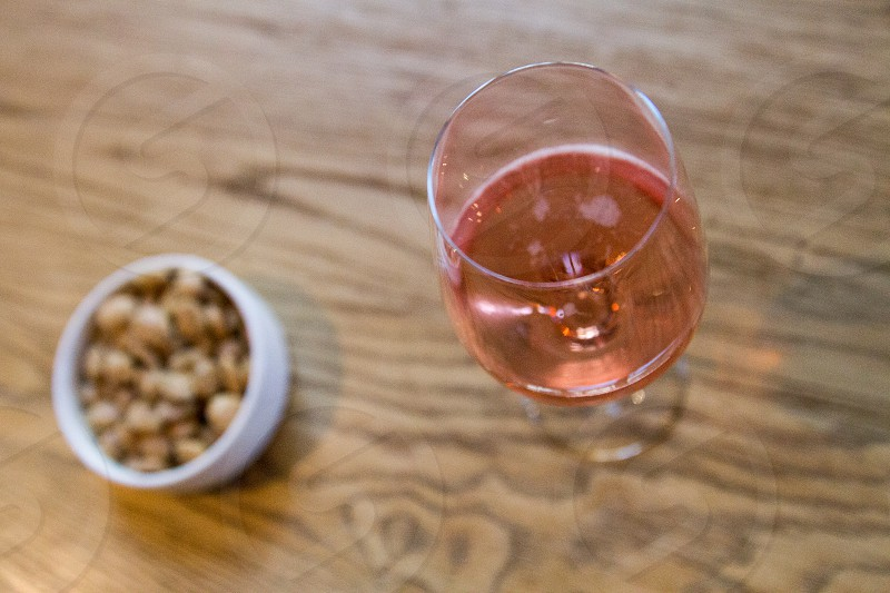 wine glass beside peanuts in round bowl in focus photography photo
