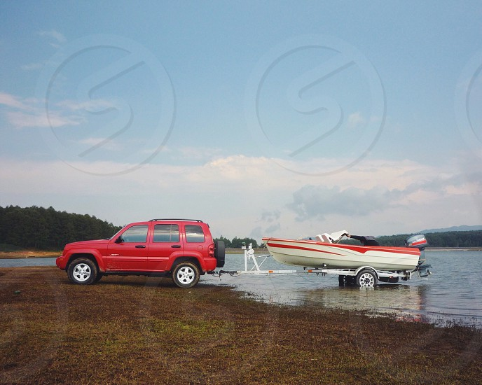 Preparing for go to adventure man checking his boat red jeep lake summer photo