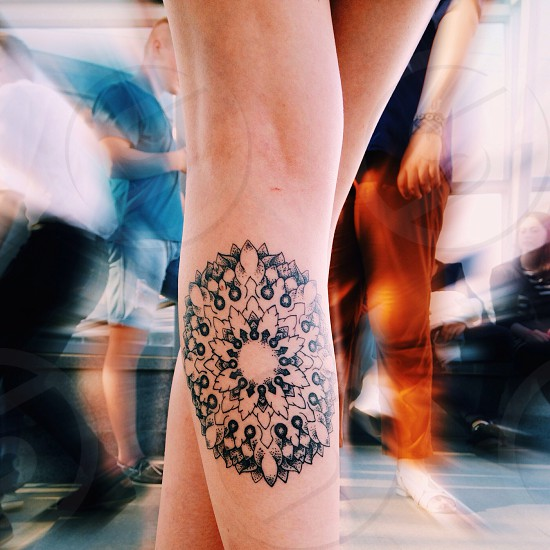 person with black floral tattoo on left leg standing surrounded by people photo