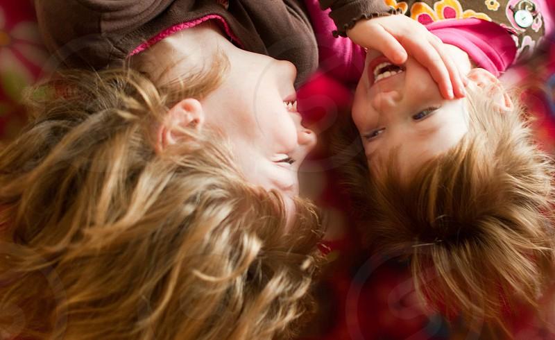 2 girls lying on pink textile laughing photo