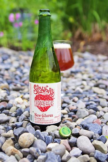 Strawberry New Glarus glass bottle on top of stone ground photo
