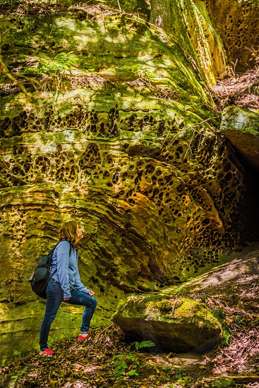 Female backpacker looking at honeycomb rock formations in Hocking Hills State Park in Logan Ohio. photo