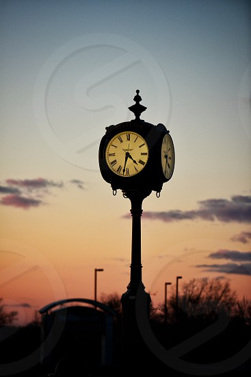 Time stands still on the clock hands of another passing day at sunset photo