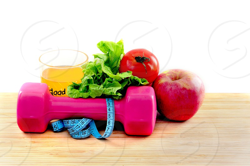 Healthy food healthy drink dumbbell and body ruler measuring tape on wooden table for fitness concept isolated white background photo