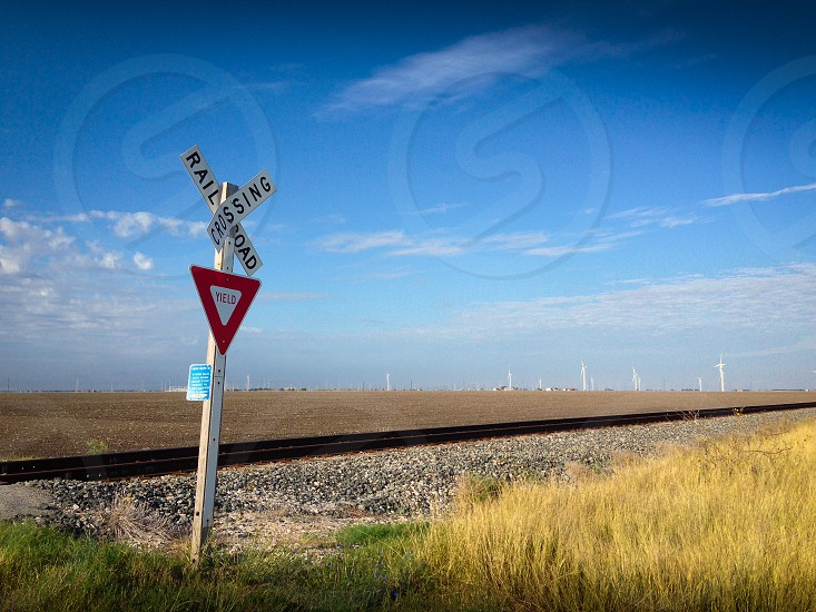 railroad crossing sign with a railroad track behind it photo