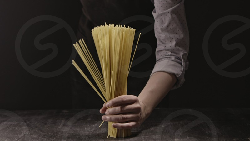 Female hand is holding raw spaghetti pasta as a bouquet on a wooden table on a black background. Slow motion Full HD video 240fps 1080p. photo
