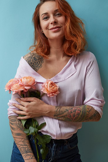 A happy girl with a tattoo is holding pink roses media on a blue background. Happy Valentine's Day photo