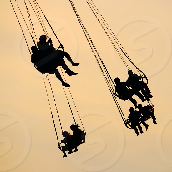 people riding tall swing amusement park ride photo