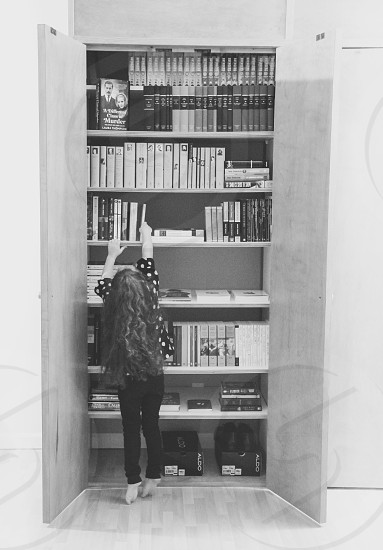 grayscale photograph of a girl reaching a book from the book shelf photo