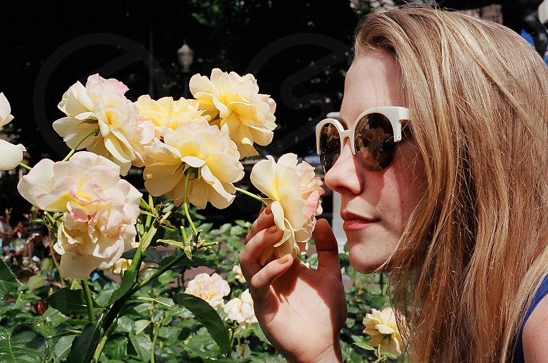 woman smelling yellow flower photo