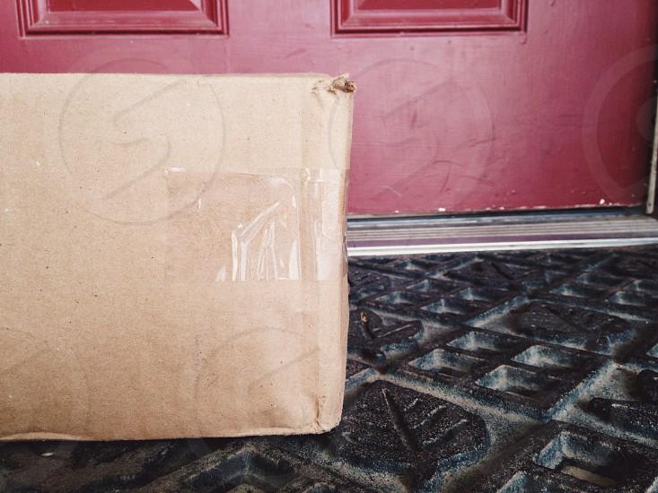 brown card board box near door photo