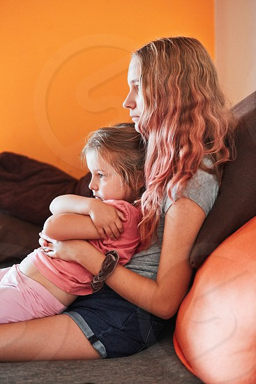 Teenage girl and her little sister watching TV together sitting concentrated on sofa at home. Real people authentic situations photo
