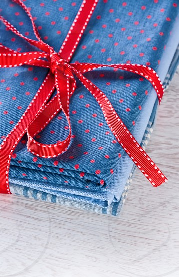 Blue fabric pile with red ribbon photo