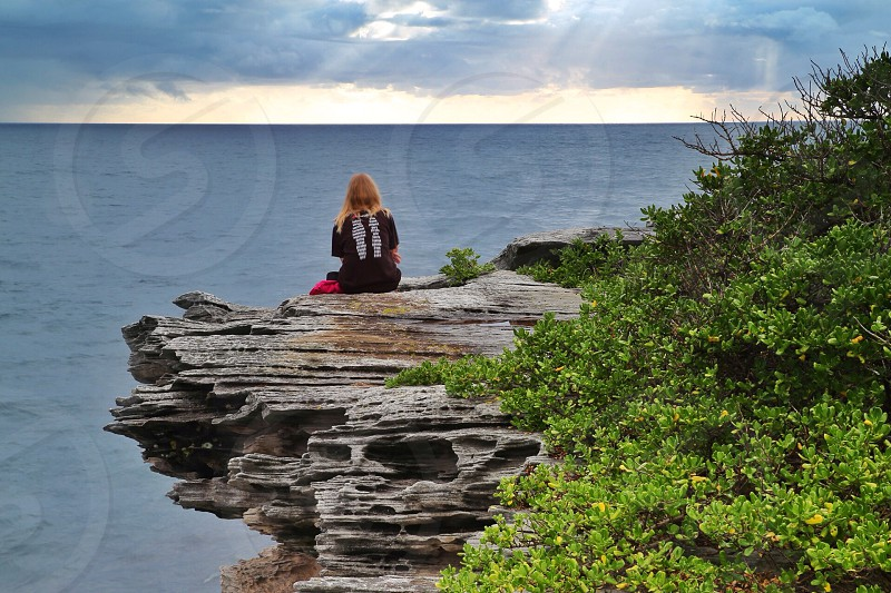woman sitting on rock formation near body of water photo