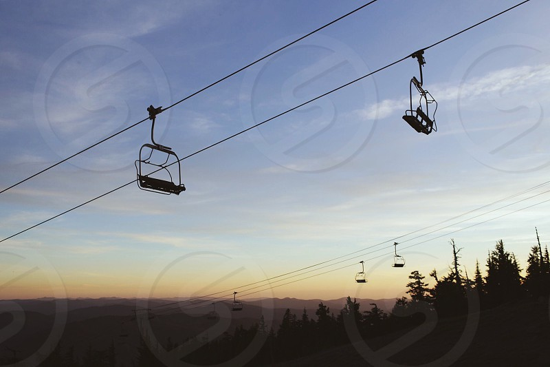 cable cars over trees under blue sky during daytime photo