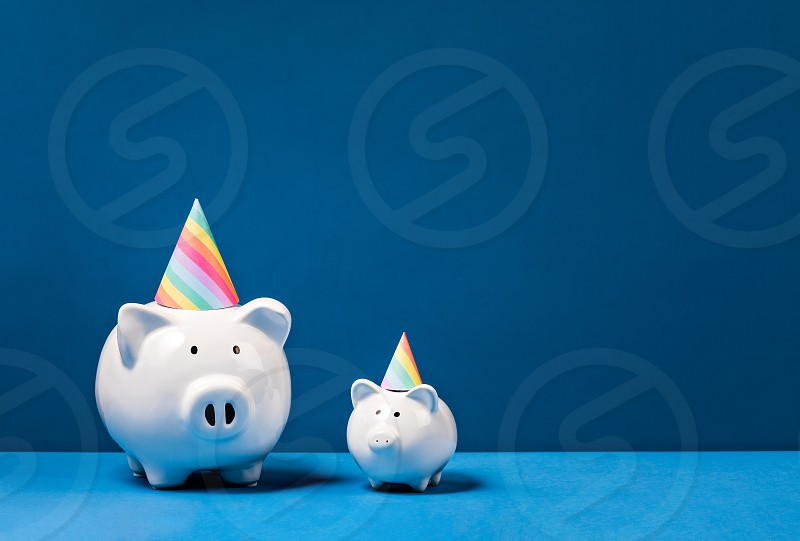 Piggy Banks wearing birthday hats over a blue background. Birthday Money Concept. photo