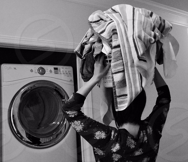 woman carrying basket of laundry in front of washing machine grayscale photography photo